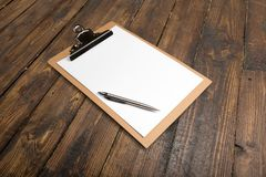Tablero del papel en blanco en la tabla de madera Imagen de archivo libre de regalías