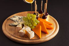 Tablero del queso con la miel Foto de archivo libre de regalías