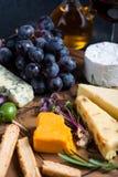 Tablero del queso con las uvas, las hierbas y las aceitunas frescas Fotos de archivo libres de regalías