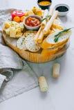 Tablero del queso con los tomates, el atasco, el baguette, las barras de pan y el crac imágenes de archivo libres de regalías