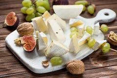 tablero determinado del queso en la tabla de madera imagen de archivo