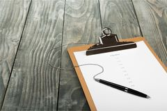 Tablero en blanco con una pluma en la tabla de madera Fotos de archivo libres de regalías