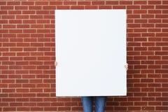 Tablero en blanco contra la pared de ladrillo lista para el texto Fotos de archivo