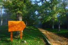 Tablero en blanco de madera en la entrada del bosque Imagenes de archivo