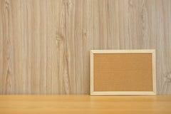 tablero en blanco del corcho en el escritorio de madera corkboard del boletín imagenes de archivo