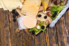 Tablero gastrónomo del queso adornado con la fruta fresca Fotografía de archivo