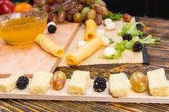 Tablero gastrónomo del queso con la fruta fresca Foto de archivo