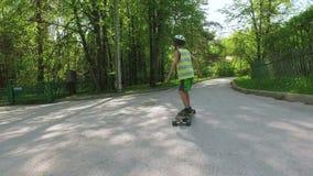 Tablero largo patinador del muchacho joven en día de verano