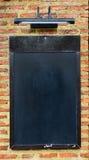 Tablero negro en la pared de ladrillo Foto de archivo