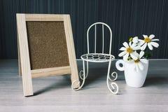 Tablero o muestra en blanco con la pequeña silla de la flor blanca y del vintage Foto de archivo libre de regalías