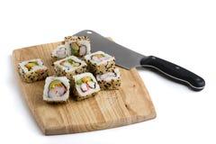 Tablero para cortar el pan con las rebanadas del sushi fotografía de archivo