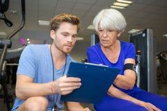 Tablero personal de la tenencia del instructor con la mujer mayor en centro de aptitud imagen de archivo libre de regalías