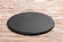 Tablero redondo del soporte de la pizarra un fondo de madera Espacio para el texto foto de archivo