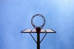 Tablero trasero de baloncesto viejo de la negligencia con el aro oxidado sobre corte de la calle Cielo azul Fotografía de archivo libre de regalías