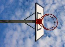 Tablero trasero de baloncesto viejo de la negligencia con el aro oxidado sobre corte de la calle Cielo nublado azul en bckground  Imagen de archivo libre de regalías