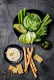 Tablero verde del bocado de las verduras con las diversas inmersiones Hummus, hummus o pesto con las galletas, grissini de la hie imagen de archivo