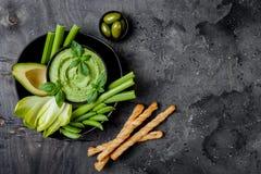 Tablero verde del bocado de las verduras con hummus de la hierba o la inmersión del pesto Disco crudo sano del aperitivo del vera fotografía de archivo