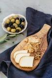 Tablero y aceitunas del queso fotografía de archivo