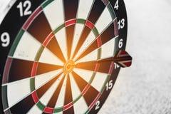Tablero y flecha de dardo en centro Concepto del negocio y del ?xito Tema del logro y de la blanco Efecto luminoso del sol anaran foto de archivo libre de regalías