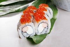Tableros blancos del caviar del sushi del rollo del camarón de Philadelphia todavía de las hojas de la vida tropical roja para el Fotografía de archivo