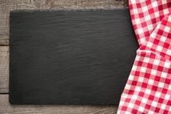 Tableros de madera rústicos, servilleta a cuadros roja y plato negro de la pizarra con el espacio de la copia para su menú o rece Fotos de archivo libres de regalías