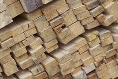 Tableros de madera y barras aserrados en un paquete en la acción Fotos de archivo libres de regalías