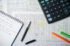 Tables with accounting calculations, paper notebook with records, calculator, pen and highlighter stock images
