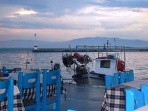 tables bleues et coucher du soleil sur la plage en Grèce Images libres de droits