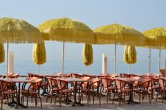 Tables, chairs and beach umbrellas, along the seashore, in Cote. Bar tables, chairs and beach umbrellas, along the seashore, in the blue coast, Menton, France Royalty Free Stock Photo