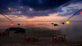 Tables Chairs on Beach under Lanterns in Dusk after Sunset stock footage