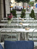 Tables and chairs at a cafe. Cafe with tables and chairs in white and steel with colorful dotted ashtrays and fresh flower outdoors in a city location royalty free stock image
