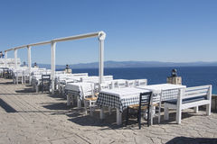 Tables with chairs in Greek tavern on sea coast royalty free stock image