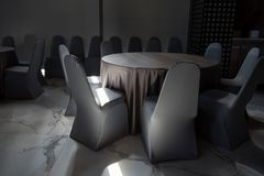Tables and chairs in hotel restaurant. Circle tables with tablecloths and chairs with light shade in restaurant of modern hotel stock photo
