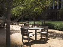 Tables and chairs on packed sand in a downtown Dallas park Royalty Free Stock Photo