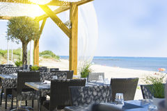 tables and chairs in the restaurant on the sea background stock photography