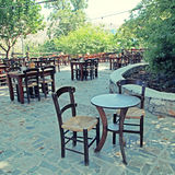 Tables and chairs of rural outdoor cafe, Greece Stock Photo