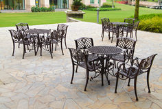 Tables and chairs on sandstone flooring at garden. Tables and chairs on sandstone flooring beside a garden. Concept of outdoor relaxation Stock Photography