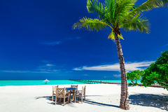 Tables and chairs in the shadow of palm tree on a tropical islan Royalty Free Stock Photo