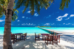 Tables and chairs in the shadow of palm tree on tropical island. Tables and chairs in the shadow of palm tree on amazing tropical island Royalty Free Stock Photos