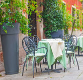 Tables and chairs. In a small square in Venice, Italy stock photos
