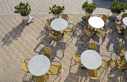 Tables and chairs in street cafe on pavement Stock Image
