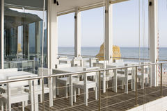 Tables and chairs in stylish restaurant. On an ocean coast, with sea view - Algarve, south of portugal Stock Images