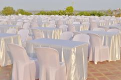 Tables and chairs with white clothes. Royalty Free Stock Photography