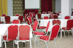 Tables and chairs. A white tables and red modern chairs Royalty Free Stock Photography