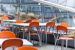 Tables and coloured chairs in a street cafe. Empty dining tables and coloured chairs in a street cafe stock photo