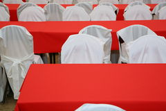 Tables covered with red tablecloths and chairs in white covers. Royalty Free Stock Photography