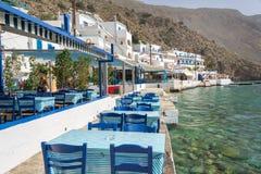 Tables de restaurant par la mer dans le village scénique de Loutro en Crète Grèce Photo stock