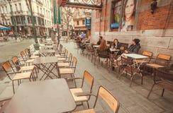 Tables de rue de café d'outddor avec des meubles, des personnes potables et de vieux bâtiments avec des restaurants Photographie stock