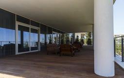 Tables de vacances, chaises, un sofa et parapluies fermés sur le porche Images libres de droits