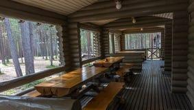 Tables et bancs en bois sur la terrasse d'une cabane en rondins Photo libre de droits